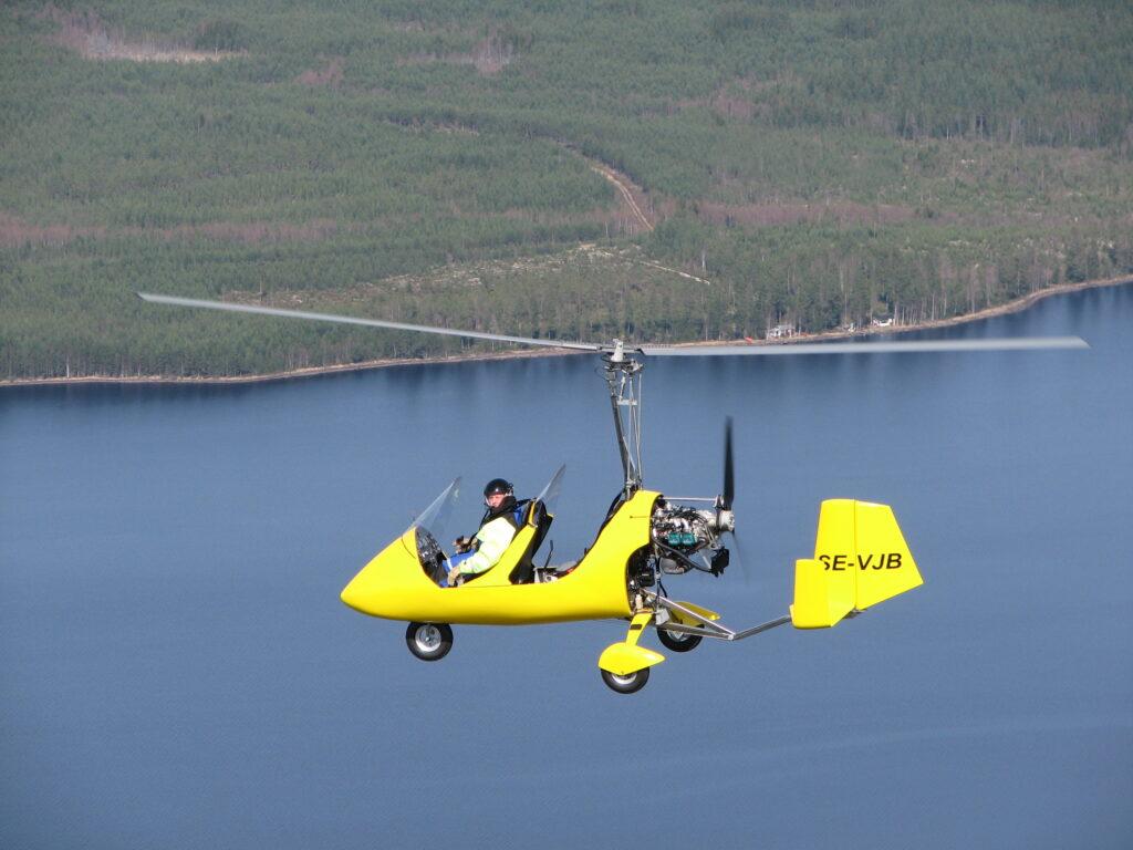 En gyrokopter flyger över sjön Siljan.